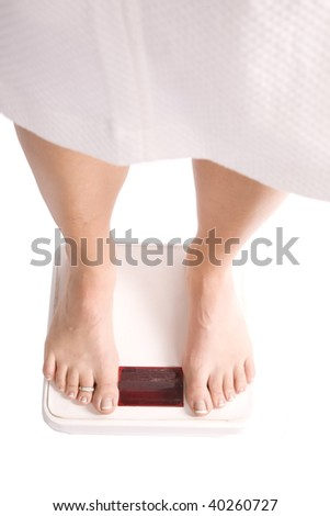 A woman in her robe weighing herself on a scale. - stock photo