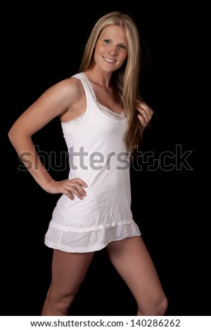 A woman in her short white dress with her hand in her hair and a smile on her lips - stock photo
