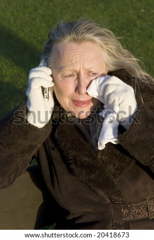 A woman in her sixties is crying as she receives bad news on her cellphone - stock photo