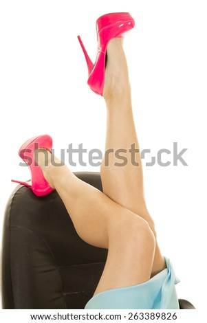 a woman in her skirt, kicking her feet up on her office chair. - stock photo