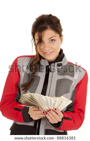 a woman in her traveling jacket with a  handful of money with  a smile on her face.