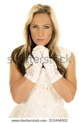 A woman in her vintage wedding dress with her hands up by her face with a serious expression. - stock photo