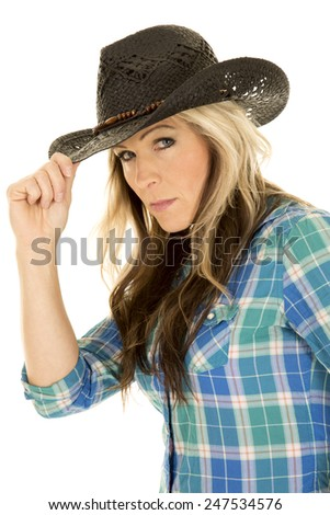 a woman in her western hat touching the brim with a serious expression on her face. - stock photo