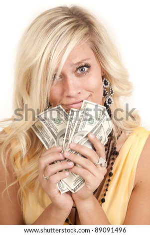 A woman in her yellow dress with a handful of money with a funny expression on her face. - stock photo