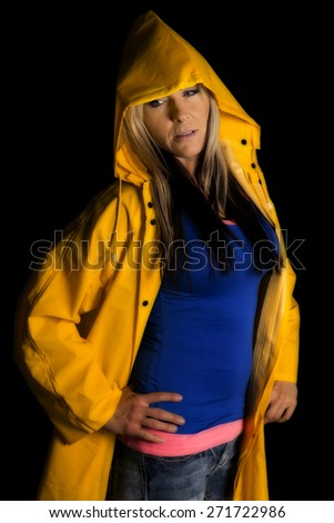 a woman in her yellow rain coat looking to the side. - stock photo