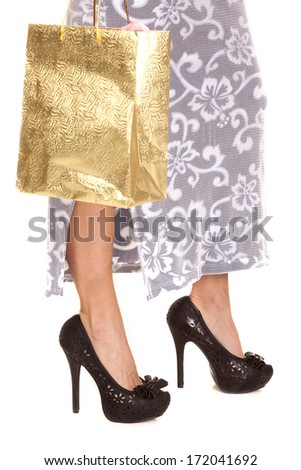 A woman in high heels legs with a shopping bag. - stock photo