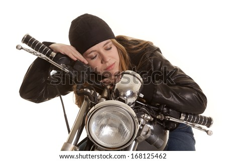 a woman in leather laying on her motorcycle asleep. - stock photo