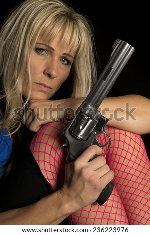 A woman in pink fishnets stockings close with a gun. - stock photo