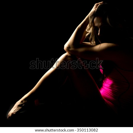 A woman in pink, sitting in the shadows with a sad emotion. - stock photo