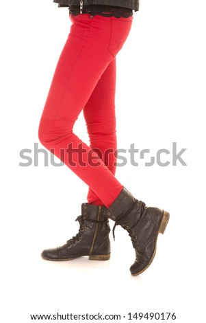 A woman in red pants in boots one on toe. - stock photo