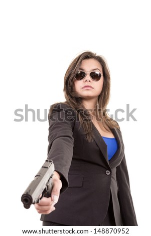 A woman in suit and sunglasses holding a gun - stock photo