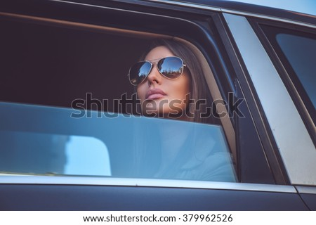 A woman in sunglasses looking through car's window. - stock photo