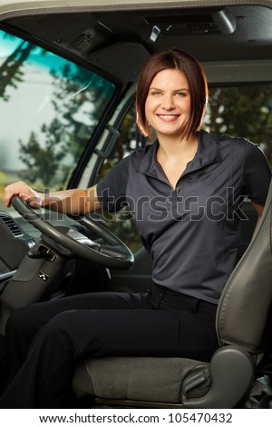 A woman in work uniform sits in the driver's seat of a delivery truck, smiling at camera. - stock photo