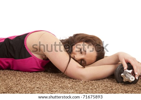 A woman is asleep on the floor by some weights. - stock photo