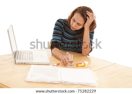 a woman is at a table with her business work and some medication. - stock photo