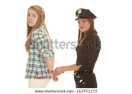 A woman is being handcuffed by a police woman. - stock photo