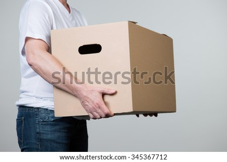 A woman is carrying a big cardboard in his hands isolated on a grey background. - stock photo