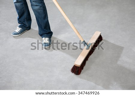 A woman is cleaning the grey floor with a broom.