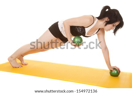 A woman is doing push ups while holding green balls. - stock photo