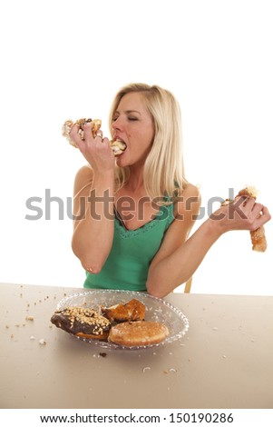A woman is eating fistfuls of doughnuts.