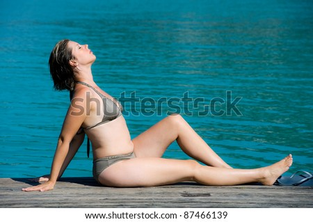 A woman is enjoying the sun while she is lying on a pier.