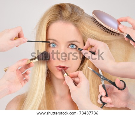 A woman is getting a makeover with many hands holding lipstick and makeup around her face. - stock photo
