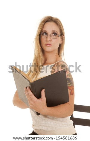 A woman is holding a book looking up to the side.