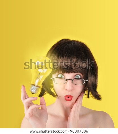 A woman is holding a light bulb and looks surprised. There is a yellow background with room for your text. The light bulb can represent an idea or success concept. - stock photo