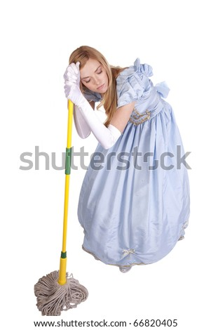 A woman is holding a mop and leaning on it looking very tired.  She is dressed like Cinderella - stock photo