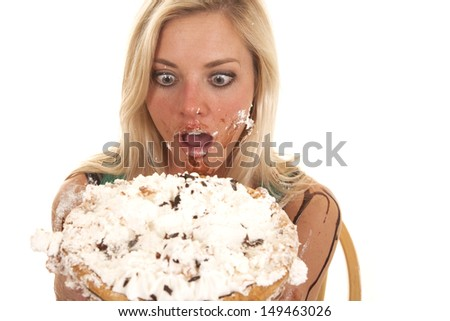 A woman is holding a pie by her face and she has it all over her. - stock photo