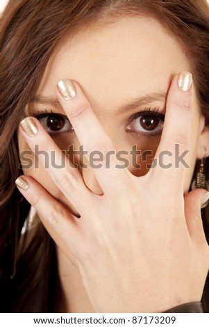 A woman is holding her hand by her face looking through her fingers.