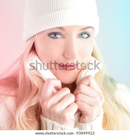 A woman is holding her winter sweater and looks into the camera with a blue and red fade representing cold and warmth. - stock photo