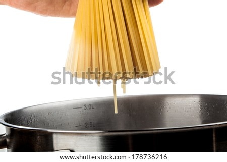 A woman is holding some pasta over a pan with hot water. - stock photo