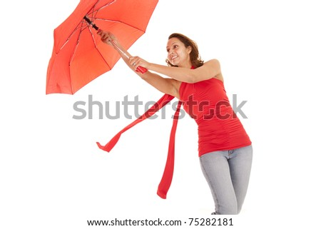 A woman is holding up an umbrella that is red.