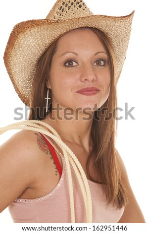 A woman is in a cowboy hat with a rope on her shoulder. - stock photo