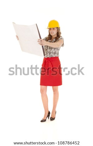 A woman is in a hard hat holding blueprints. - stock photo