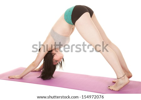 A woman is in the downward dog yoga position. - stock photo
