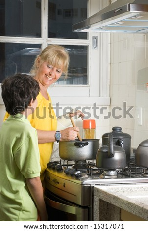 A woman is in the kitchen cooking with her son.  They are looking at each other and smiling.  Vertically framed shot.