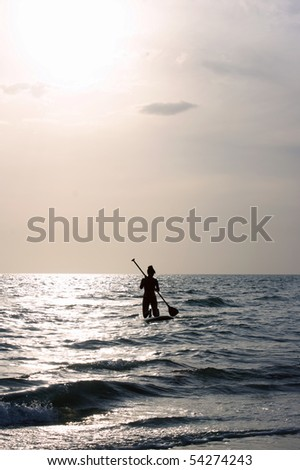 A woman is kneeling on paddleboard and is on the surface of the sea paddling towards the horizon, facing away from viewer in partial shilouette with sun in upper left corner