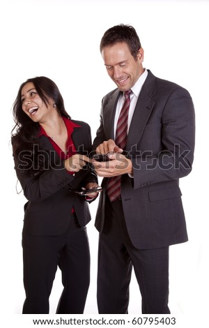 A woman is laughing at what a man shows her on his phone. - stock photo