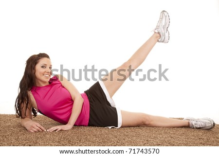A woman is laying down in fitness attire with her leg up. - stock photo
