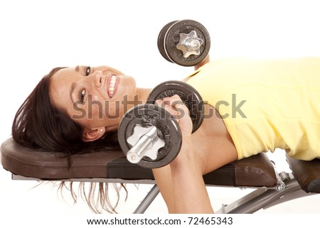 A woman is laying on a bench lifting weights. - stock photo