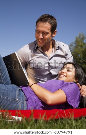 A woman is laying on the lap of a man reading a book. - stock photo
