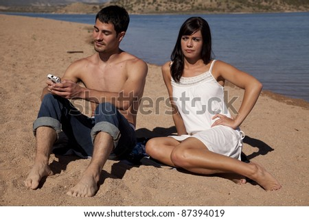 A woman is mad that her man is texting on his phone while they are at the beach. - stock photo