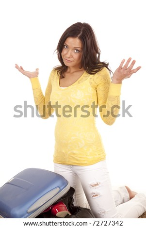 A woman is not sure how to get her suitcase closed - stock photo