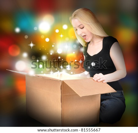 A woman is opening a box with a present inside. Sparkles and glowing are around her. Use it for a Christmas or Birthday concept. - stock photo