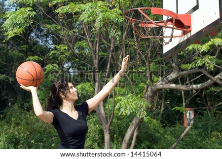 A woman is playing basketball on a court at the park.  The woman is looking at the basketball hoop and about to make a shot.  Horizontally framed photo. - stock photo
