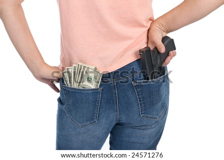A woman is prepared to defend her cash with a semi-automatic handgun. - stock photo