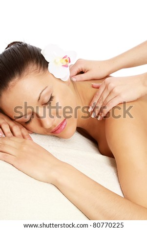 A woman is relaxing during a massage - isolated on white background, vertical - stock photo