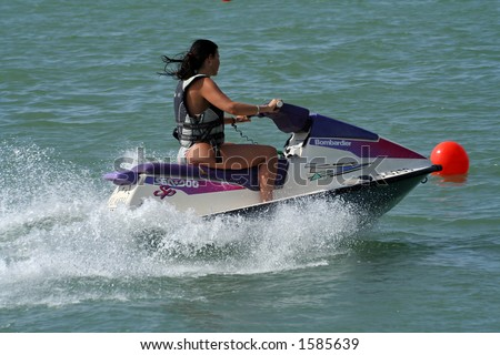 A woman is riding on a jet ski